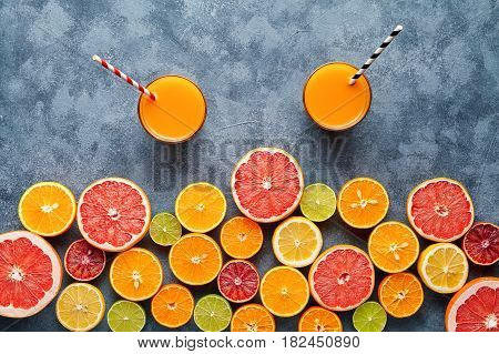 Fresh juice or smoothie vitamin detox drink in citrus fruits background flat lay on concrete table, healthy lifestyle natural organic detox diet beverage. Tropical summer grapefruit, orange, apple mix