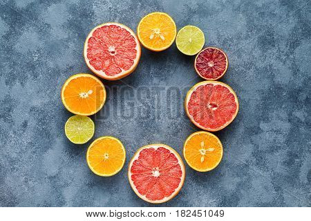 Citrus fruits sliced frame flat lay on blue concrete background blank copy design space, healthy vegetarian organic food, antioxidant detox diet. Tropical summer mix grapefruit, orange, apple mix