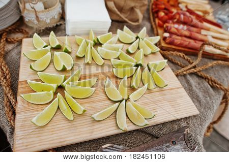 Cutted Into Slices Lime On Wood Board At Wedding Catering Table.