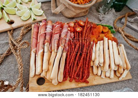 Salted Sticks With Ham And Bavarian Sausages On Wooden Board At Catering Wedding.
