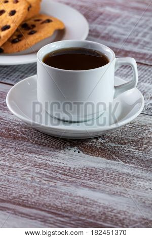 cup of coffee with a thin captain on a wooden table