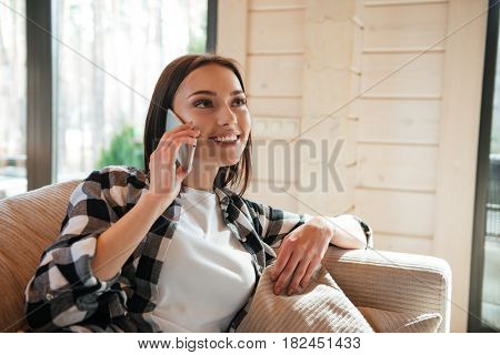 Portrait of cheerful young woman talking on phone looking up and sitting on sofa in living room