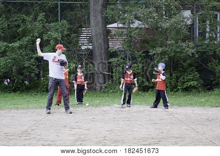 Montreal, Quebec - May 18, 2015 -- Wide view of little league baseball players practicing with their coaches in a park in Montreal, Quebec on a bright day in May.