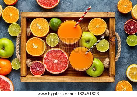 Different citrus fruit in a wooden tray and grey concrete table. Fruit food background.Antioxidant, detox, dieting, clean eating, vegetarian, vegan, fitness or healthy lifestyle concept. Flat lay.