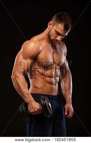 Handsome power athletic man with dumbbell is confidently looking forward. Strong bodybuilder with six pack, perfect abs, shoulders, biceps, triceps and chest Isolated on black background with copyspace.