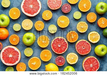 Organic fruit food background. Citrus pattern on grey concrete table. Healthy eating and diet. Antioxidant, detox, dieting, clean eating, vegetarian, vegan, fitness or healthy lifestyle concept