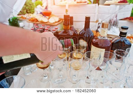 Hand Of Waiter Who Pours Drinks At Glasses On Wedding Reception.