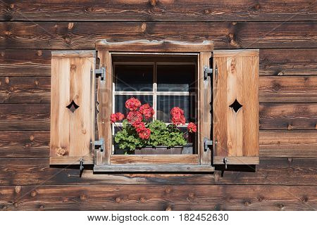 farmstead window with wooden shutters and red pelargonium flowers