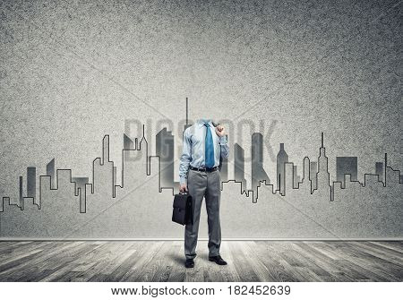 Headless engineer man with briefcase in hand against construction background