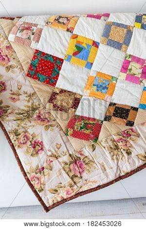 Part of color patchwork quilt with vintage flowers pattern lying on a white sofa as background. Colorful Scrappy blanket. Hobby concept.