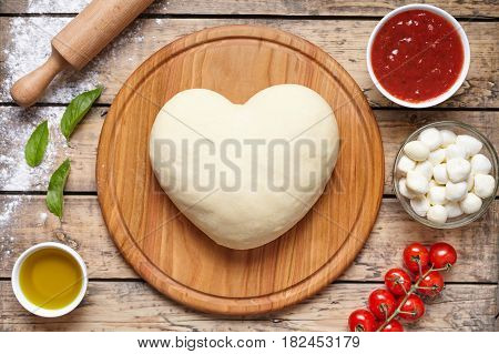 Heart shaped pizza cooking ingredients. dough, mozzarella, tomatoes, basil, olive oil, cheese, sauce, spices. Work with the dough. Top view Flat lay Romantic love food concept