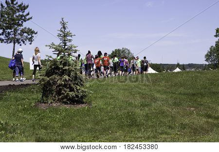 Laval, Quebec - June 14, 2015 - Landscape view from the back of people walking on a path towards the finish at the