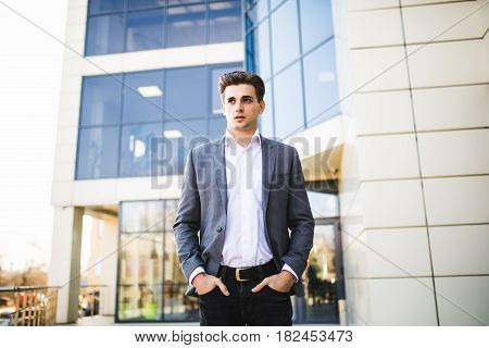 Elegant Handsome Young Businessman While Walking In Front Of Office Building