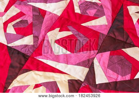 Part of color patchwork quilt with purple flowers pattern as background. Pink Scrappy blanket. Hobby Concept. abstract flowers background.