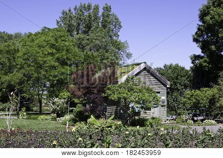 Laval, Quebec - June 14, 2015 - Landscape view of a small wooden garden house surrounded by trees foliage and a small garden in the Nature Park, Laval, Quebec on a sunny day in June.