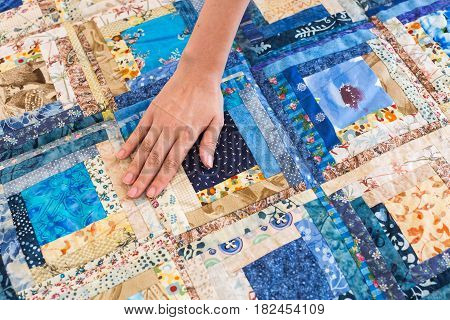 The caucasian female hand touching a color patchwork quilt with blue geometry pattern. Part of Colorful Scrappy blanket close up. dream concept