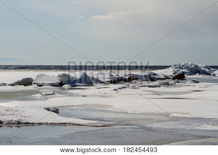 Russia. Leningrad region. - Ice drift on the Gulf of Finland. Ice hummocks and water along the coastline