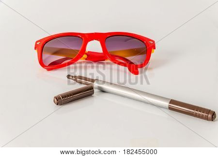 Brown marker pen with red sunglasses color highlighter school tools white background
