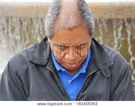 African american male senior expressions alone outside.