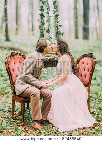 The kissing vintage dressed newlyweds sitting on the old stylish orange chairs in the front of the hanging stump with the green, white and strawberry cake in the green spring wood