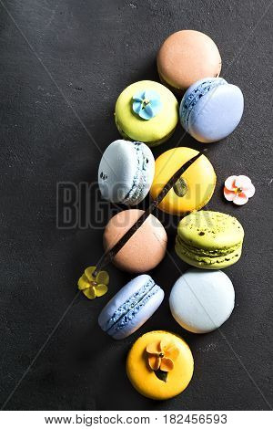 Assorted colorful french cookies macaroons on a black background. Space for text. Closeup. Top view. Concept of the baking macaroons