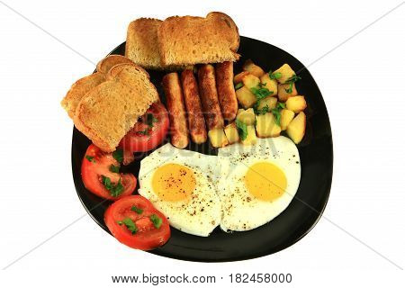 Breakfast of fried sausages potatoes eggs sliced tomatoes seasoned with parsley leaves and ground black pepper and served with toast on a black dish over a white background
