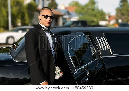 Handsom young man in tuxedo standing by his Limousine going out on the town
