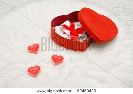 Open red box with heart shaped red and white linen a white fur. Heart shaped candles