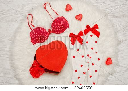 Fashion concept. Red box heart shaped with lace lingerie white stockings with bows red bra red heart shaped candles on a white fur.