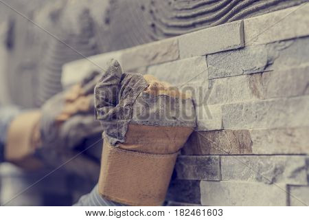 Retro effect faded and toned image of hands of tiler worker in gloves pressing brick tiles to stick it to the wall.