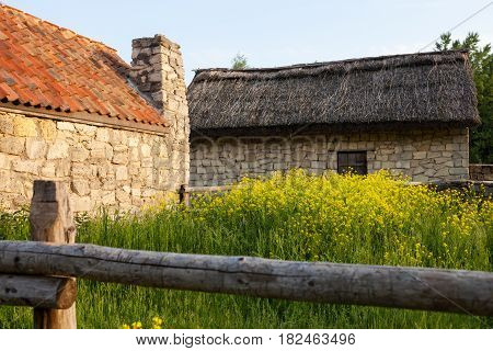 Old sandstone houses under the thatched roof and under the roof covered with orange tiles. Traditional Ukrainian architecture.