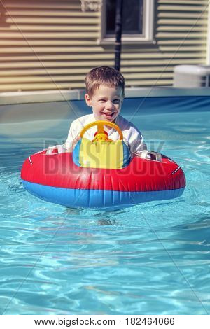 Happy boy in a pool with inflatable raft