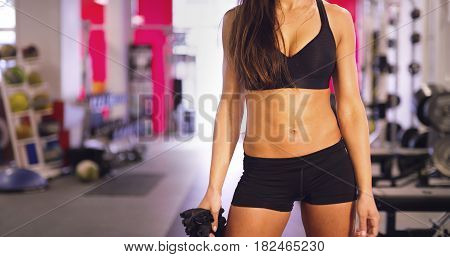 Cropped portrait image of beautiful athletic woman with a fit body in fitness gym. Well trained stomach with sixpack. Holding gloves.
