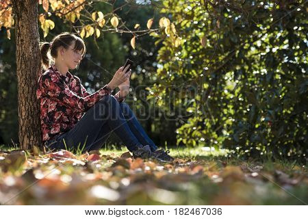 Young woman sitting under an autumn tree in a park reading something on a digital device or mobile phone.