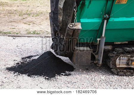 Paver working on the road construction. Dumping new asphalt on the road bed covered with crushed stones. Close-up.