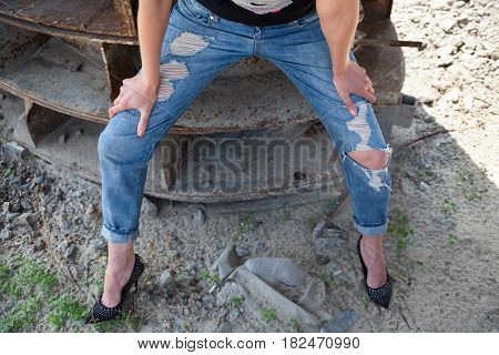 Woman in ragged jeans and black stiletto-heeled shoes sitting on the rusty metal construction.