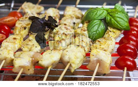 Raw skewered meat with tomatoes and basil on the grill. Close-up.