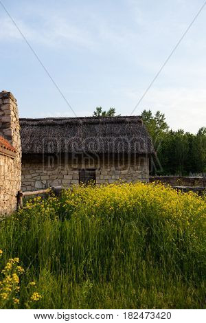 Old sandstone house under the thatched roof. Traditional Ukrainian architecture.