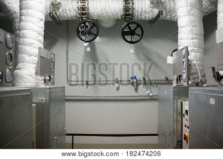 Industrial plant. Interior. White insulated pipes black valves gray metal containers and control panels.