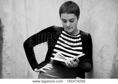 A Girl With Big Eyes And Short Hair Reads A Book, Standing By The Wall. Preparing For Exams At The U
