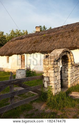 Wattle and daub house under the thatched rood. Sandstone fence and wooden gate. Traditional Ukrainian architecture.