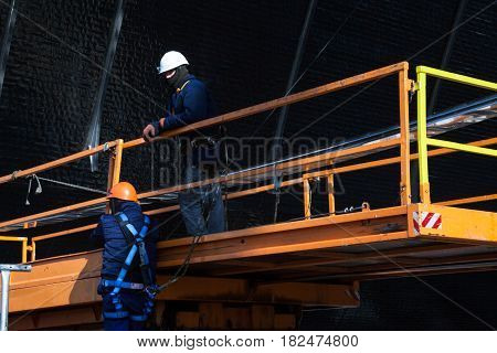 CHERNOBYL UKRAINE - OCTOBER 16 2015: Builders working on construction of New Safe Confinement (or New Shelter) at Chernobyl Nuclear Power Plant over the nuclear reactor destroyed by Chernobyl disaster in 1986.
