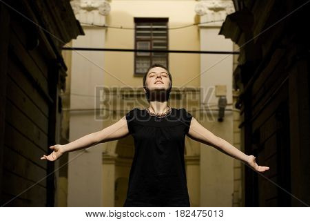 A Girl With Short Hair Is Enjoying The Sun, Standing In The Courtyard Of The House. She Stands, Rais