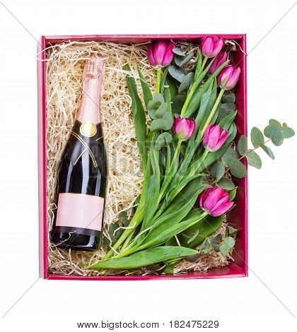 Gift box with bottle of champagne and bouquet of tulips inside