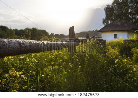 Ukrainian village. Wooden fence. Wattle and daub house under the thatched roof in the background. Rural landscape before the rain.