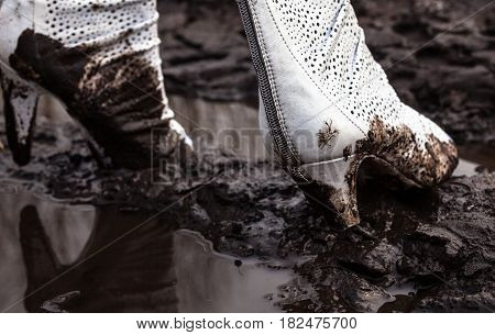 Dirty white high-heel shoes in the mud on the dirt road. Close-up.