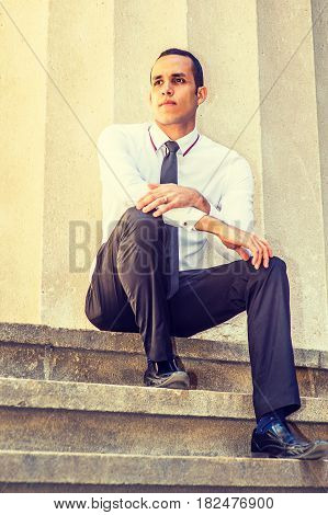Young American businessman wearing white shirt black tie pants leather shoes sitting on stairs outside office building in New York taking work break thinking lost in thought. Filtered effect