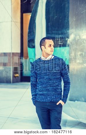 Young American Man wearing blue patterned knit sweater black pants two hands putting in pockets standing by metal mirror in New York looking away.