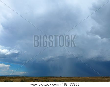 Super cell storm with a huge down burst of rain rain in the middle.  Clear blue skies with white clouds in the background.