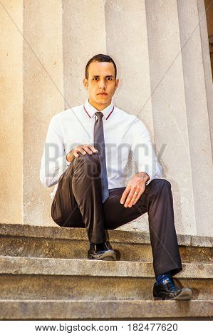 Young American Businessman wearing white shirt black tie black pants leather shoes sitting on stairs outside office building in New York taking work break thinking. Filtered effect